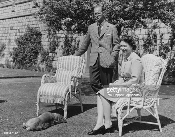 Queen Elizabeth II and Prince Philip Duke of Edinburgh pictured sitting on lawn chairs with the Queen's corgi 'Sugar' below the East Terrace of the...