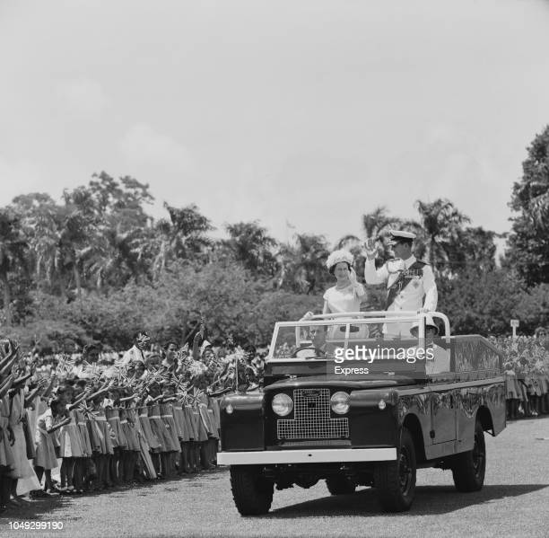 Queen Elizabeth II and Prince Philip, Duke of Edinburgh pictured waving to crowds of cheering school children from the rear of an open top Land Rover...