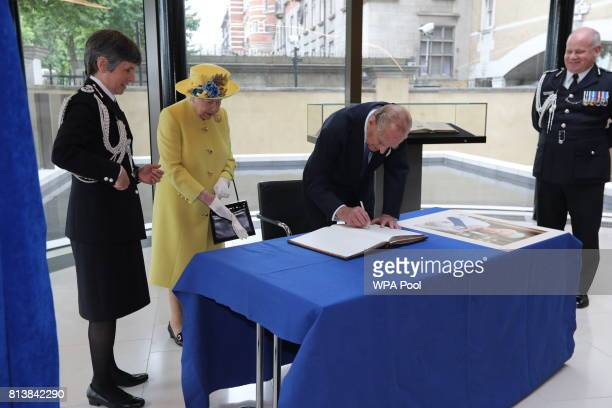Queen Elizabeth II and Prince Philip Duke of Edinburgh sign a book watched by Commissioner of the Metropolitan Police Cressida Dick and Deputy...