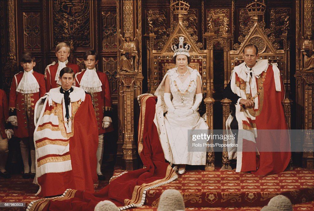 Queen Elizabeth II and Prince Philip, Duke of Edinburgh sit on their thrones as the Queen delivers the Queen's Speech in the House of Lords chamber during the State Opening of Parliament in 1970. Prince Charles sits to the left of the monarch.
