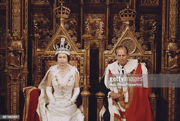 Queen Elizabeth II and Prince Philip Duke of Edinburgh sit on their thrones as the Queen delivers the Queen's Speech in the House of Lords chamber...