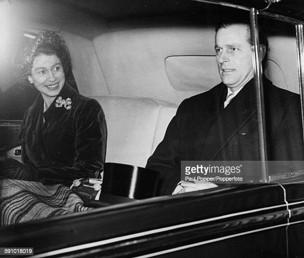 Queen Elizabeth II and Prince Philip Duke of Edinburgh smile as they ride in the back of a car after attending the wedding of Lady Palmer and...