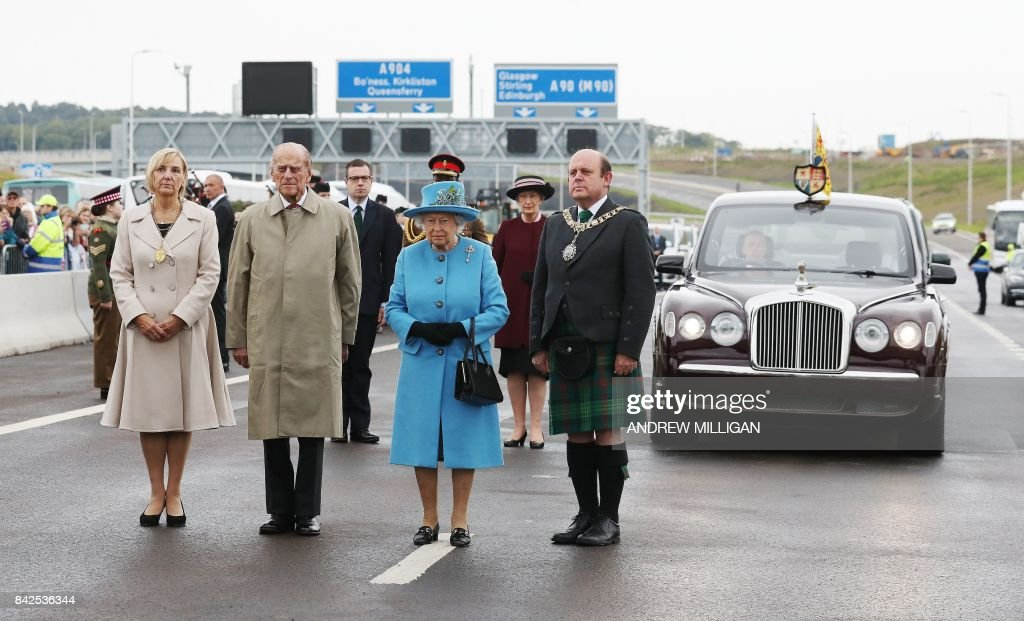 TOPSHOT - Queen Elizabeth II (C) and Prince Philip, Duke of Edinburgh (2L) stand during the official opening ceremony for the Queensferry Crossing, a new road bridge spanning the Firth of Forth from Queensferry to North Queensferry, in Queensferry, west of Edinburgh, on September 4, 2017. The new crossing, which is the longest three-tower, cable-stayed bridge in the world, and unlike the existing bridge, is expected to remain open in all weathers. PHOTO / POOL / Andrew Milligan