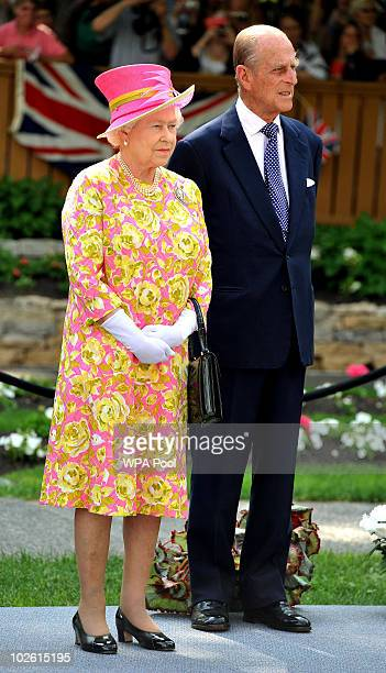 Queen Elizabeth II and Prince Philip Duke of Edinburgh stand in the garden of Government House where the Queen unveiled a statue of herself on July 3...