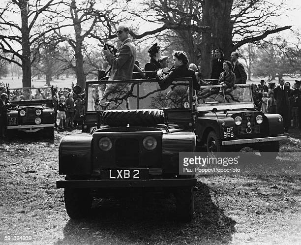 Queen Elizabeth II and Prince Philip Duke of Edinburgh stand on the front seats of an open top Land Rover as they watch the Olympic Horse Trials at...