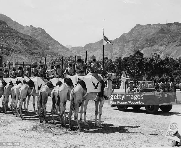 Queen Elizabeth II and Prince Philip Duke of Edinburgh stand together in the back of a Land Rover as they inspect a guard of Camel and Armored Units...