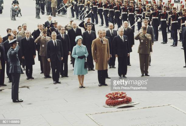 Queen Elizabeth II and Prince Philip Duke of Edinburgh stand together with officials during a wreath laying ceremony in front of the Tomb of the...