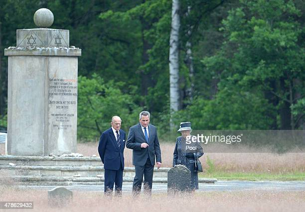 Queen Elizabeth II and Prince Philip Duke of Edinburgh stand with JensChristian Wagner director of the memorial next to the grave of Anne Frank...