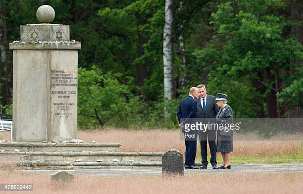 Queen Elizabeth II and Prince Philip Duke of Edinburgh stand with JensChristian Wagner director of the memorial next to the Jewish cenotaph during...