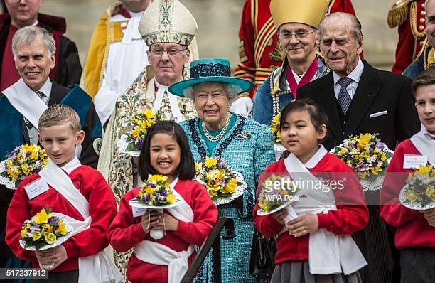 Queen Elizabeth II and Prince Philip Duke Of Edinburgh stand with local children on the steps of St Georges Chapel following the traditional Royal...
