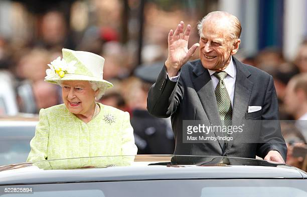 Queen Elizabeth II and Prince Philip, Duke of Edinburgh travel through Windsor in an open top Range Rover after her 90th Birthday Walkabout on April...