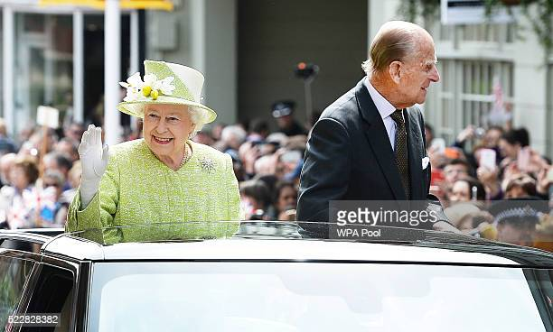 Queen Elizabeth II and Prince Philip Duke of Edinburgh travel through Windsor in an open top Range Rover after her 90th Birthday Walkabout on April...
