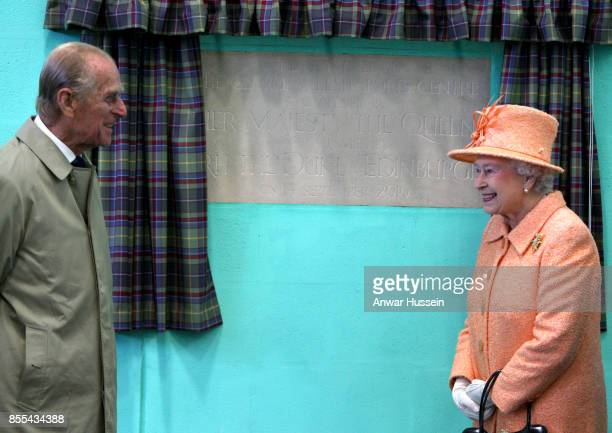Queen Elizabeth II and Prince Philip Duke of Edinburgh unveil a plaque during a visit to Gordonstoun School to open a new sports hall on September 14...