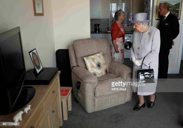 Queen Elizabeth II and Prince Philip Duke of Edinburgh view a flat belonging to Pauline Stainsby during a visit to Priory View an independent living...