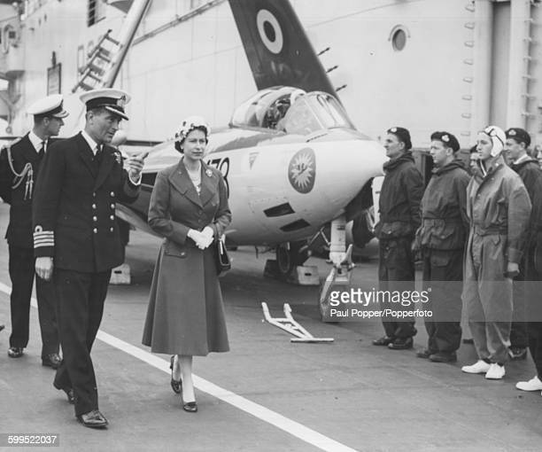 Queen Elizabeth II and Prince Philip Duke of Edinburgh walk along the flight deck of the aircraft carrier HMS Ark Royal with Captain Frank Hopkins...