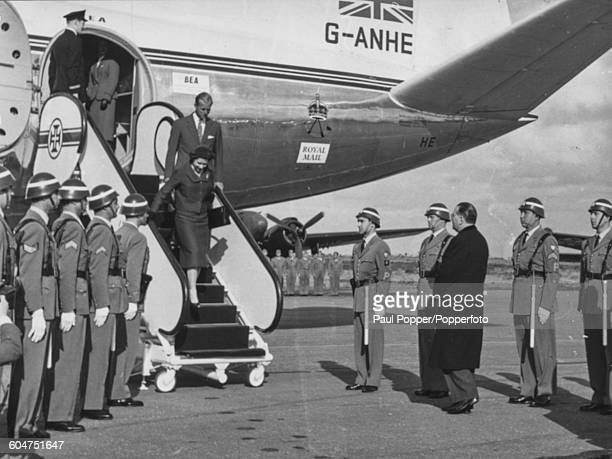 Queen Elizabeth II and Prince Philip Duke of Edinburgh walk down the steps of their Viscount aircraft to be greeted by Portuguese Foreign Minister...
