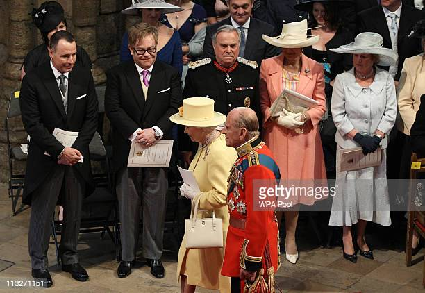 Queen Elizabeth II and Prince Philip Duke of Edinburgh walk past Elton John and David Furnish as they arrive for the Royal Wedding of Prince William...
