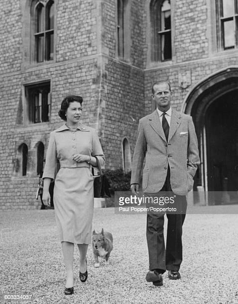 Queen Elizabeth II and Prince Philip Duke of Edinburgh walk together near the George IV Gateway with 'Sugar' the Queen's corgi at Windsor Castle...