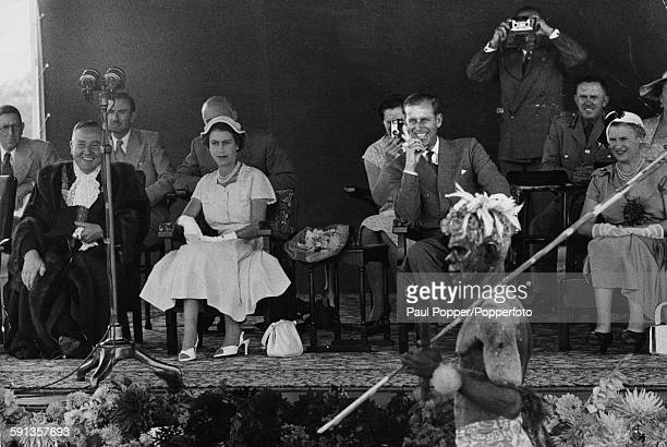 Queen Elizabeth II and Prince Philip Duke of Edinburgh watch an aboriginal display and wallaby dance at the Exhibition Grounds in Brisbane during the...