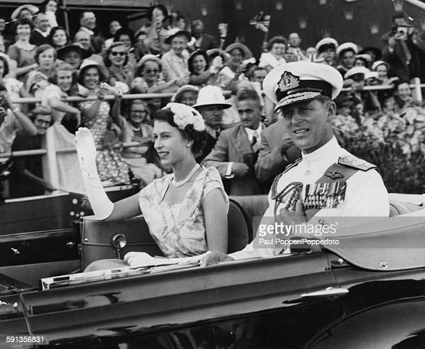 Queen Elizabeth II and Prince Philip Duke of Edinburgh wave from an open carriage as they drive past crowds of spectators at the Exhibition Grounds...