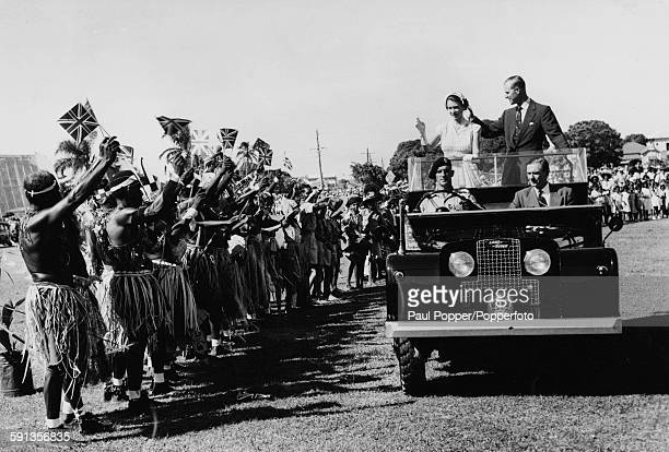 Queen Elizabeth II and Prince Philip Duke of Edinburgh wave to a group of traditionally dressed aborigines who are holding up Union Jack Flags as the...