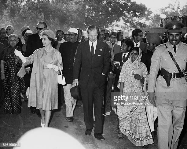 Queen Elizabeth II and Prince Philip Duke of Edinburgh wave to spectators and residents as they walk along a road to visit the Bakrota community...