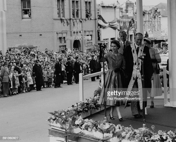 Queen Elizabeth II and Prince Philip Duke of Edinburgh wave to crowds of spectators as they accompany the Mayor and Mayoress of Wollongong on to the...
