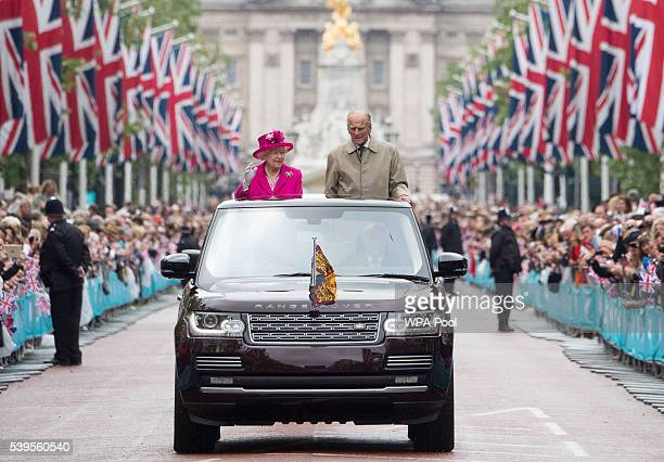 Queen Elizabeth II and Prince Philip Duke of Edinburgh wave to guests attending The Patron's Lunch celebrations for The Queen's 90th birthday on The...