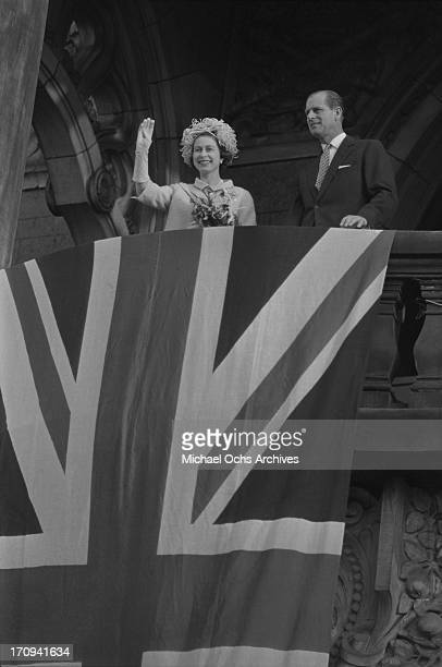 Queen Elizabeth II and Prince Philip Duke of Edinburgh wave to the crowds from a bacony behind a draped Union Jack flag on May 28 1965 in West Berlin...