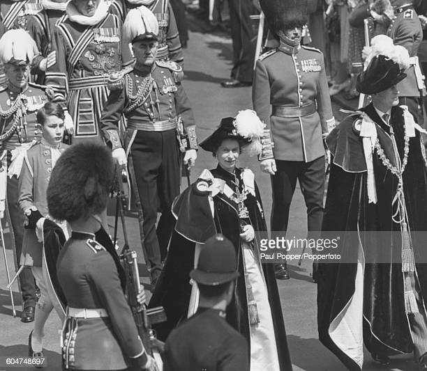 Queen Elizabeth II and Prince Philip Duke of Edinburgh wearing the traditional robes and caps of the Order of the Garter as they lead a procession at...
