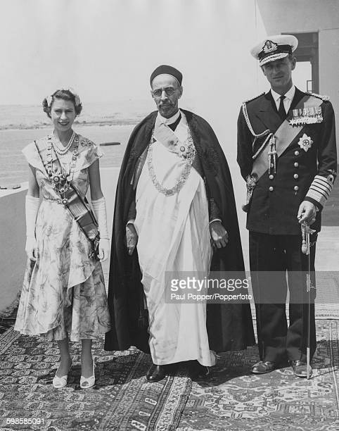 Queen Elizabeth II and Prince Philip Duke of Edinburgh with King Idris of Libya posed together on a balcony at the Royal Palace during the Royal tour...