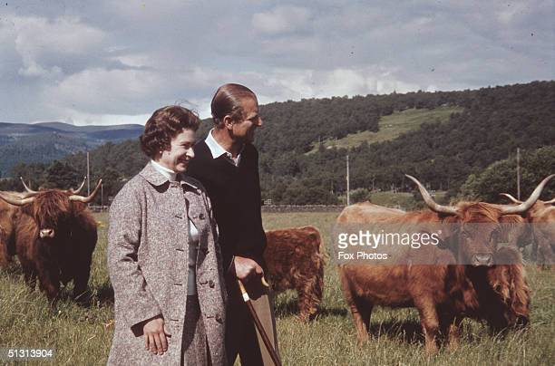 Queen Elizabeth II and Prince Philip in a field with some highland cattle at Balmoral, Scotland, 1972.