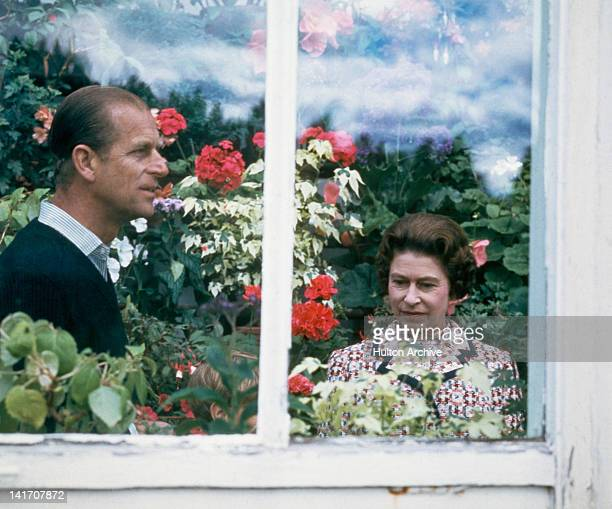 Queen Elizabeth II and Prince Philip in a greenhouse at Balmoral in Scotland, 1972. A small boy is just visible between them.