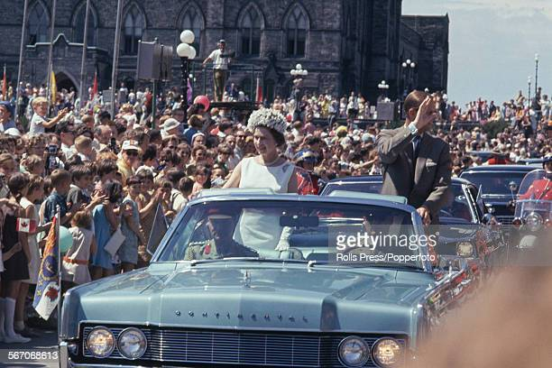 Queen Elizabeth II and Prince Philip Mountbatten Duke of Edinburgh pictured standing and waving from the rear seats of an open top Lincoln...