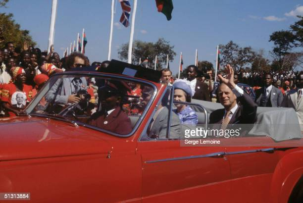 Queen Elizabeth II and Prince Philip on a royal tour of Malawi 1979 A woman on the left wears a picture of the country's president Dr Hastings Banda