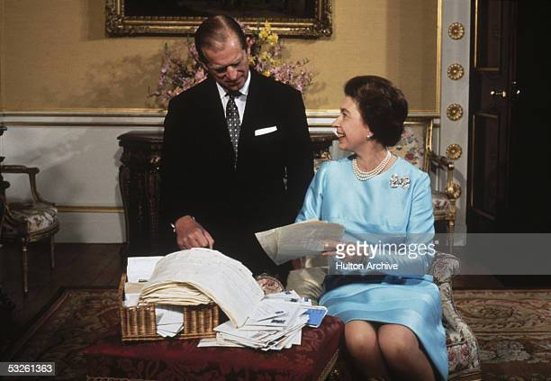 Queen Elizabeth II and Prince Philip sort through a basket of mail on the occasion of their 25th wedding anniversary 1972