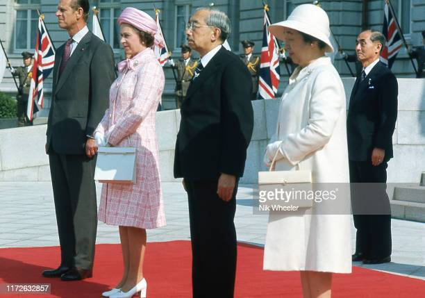 Queen Elizabeth II and Prince Philip stand with Emperor Hirohito and Empress Nagako at welcoming ceremonies in Tokyo during the Royal Tour of Japan...