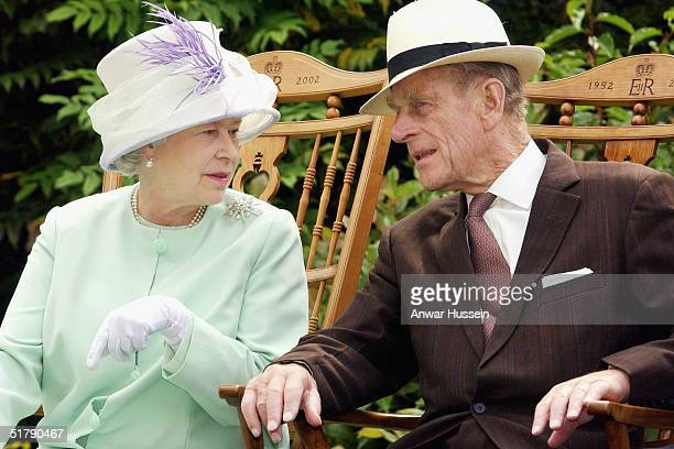 Queen Elizabeth II and Prince Philip, the Duke of Edinburgh chat while watching a musical performance in the Abbey Gardens during her Golden Jubilee...