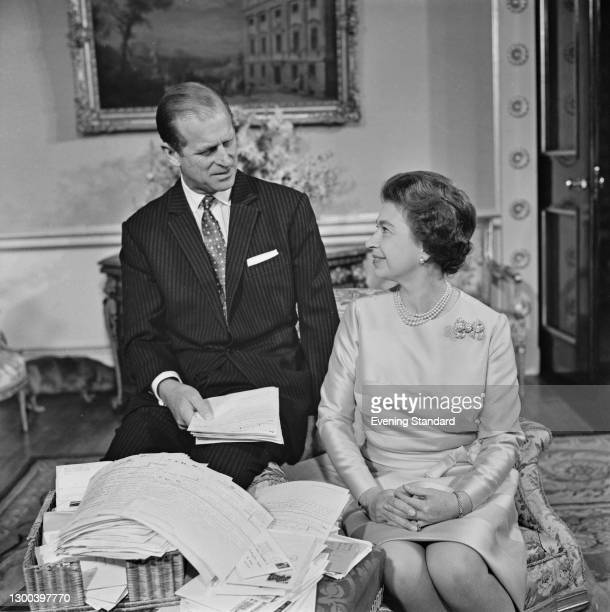 Queen Elizabeth II and Prince Philip, the Duke of Edinburgh sort through their mail on their 25th wedding anniversary at Buckingham Palace in London,...