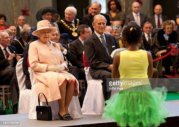 Queen Elizabeth II and Prince Philip, the Duke of Edinburgh watch performers during a visit to the Manchester Central Convention Centre on March 23,...