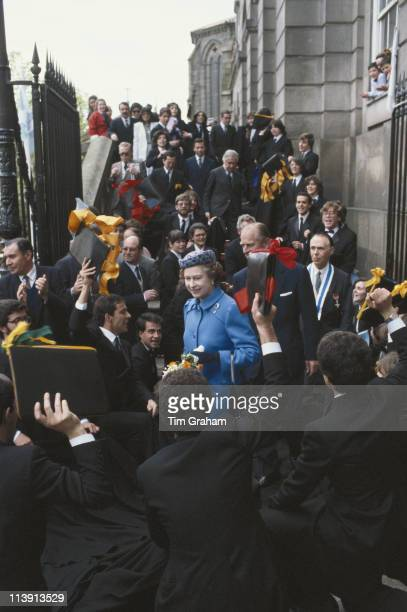 Queen Elizabeth II and Prince Philip walking through crowds of people in Oporto during their fiveday state visit to Portugal 29 March 1985