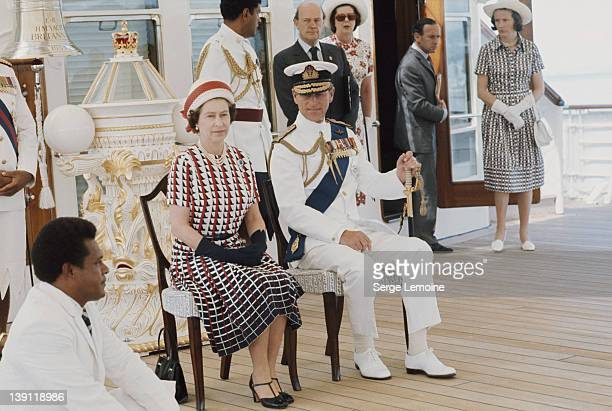 Queen Elizabeth II and Prince Philip watch the entertainments aboard the Royal Yacht 'Britannia' upon their arrival in Fiji during their royal tour...