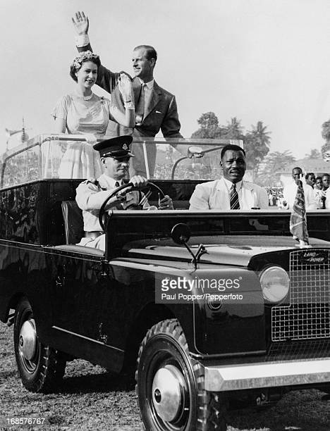 Queen Elizabeth II and Prince Philip wave from an open Land Rover to the crowds at a racecourse in Lagos during an official visit to Nigeria 12th...
