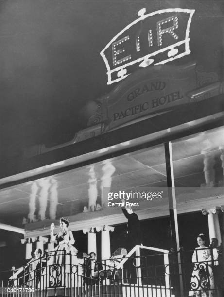 Queen Elizabeth II and Prince Philip wave to crowds from the balcony of the Grand Pacific Hotel in Suva Fiji where a ball is being held in honour of...