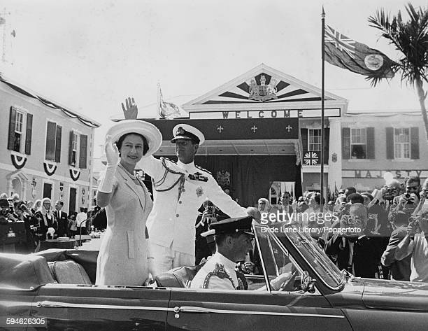 Queen Elizabeth II and Prince Philip wave to crowds from their car on their arrival in Nassau Bahamas during the royal visit to the Crown Colonies of...