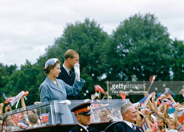 Queen Elizabeth II and Prince Philip waving to a crowd of children in Bathurst New South Wales Australia during their royal tour February 1954
