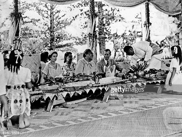 Queen Elizabeth II and Prince Philip with the Queen of Tonga at a feast at which a roasted pig was placed in front of every person, during the Royal...