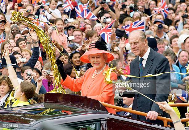Queen Elizabeth II and Prince Phillip the Duke of Edinburgh ride along the Mall in an open top car on their way to watch a parade in celebration of...