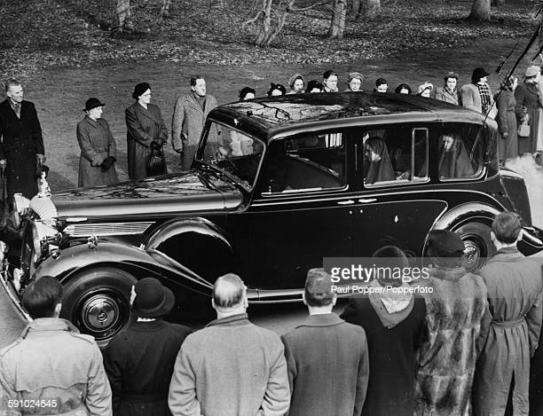 Queen Elizabeth II and Princess Margaret wear black veils as their car drives pass well wishers lining the streets to follow the funeral cortege of...