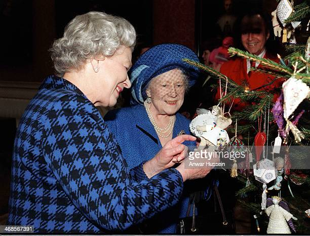 Queen Elizabeth II and Queen Elizabeth, The Queen Mother admire Christmas decorations on the Christmas tree in the Picture Gallery at Buckingham...